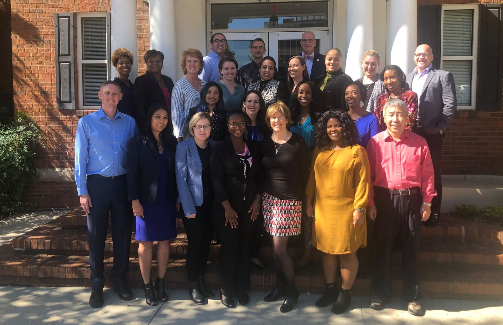 An outdoor group photo of the NACDD team.