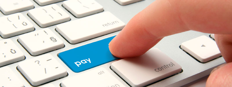 A finger hitting the 'pay' key on a computer keyboard