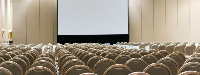Countless perfectly arranged chairs in a presentation room.