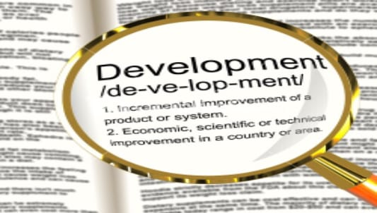 An image of a magnifying glass over the word 'development' in the dictionary.