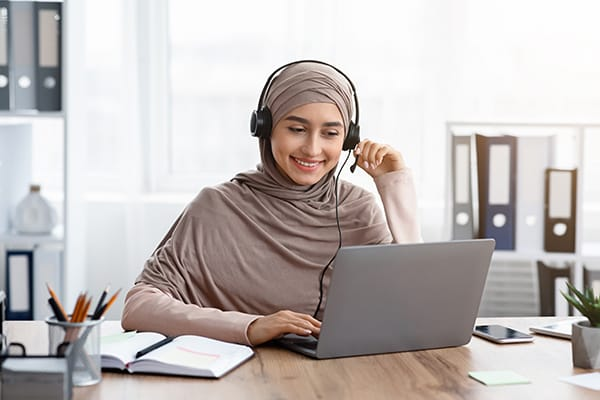 A woman happily conducts business while at her computer.