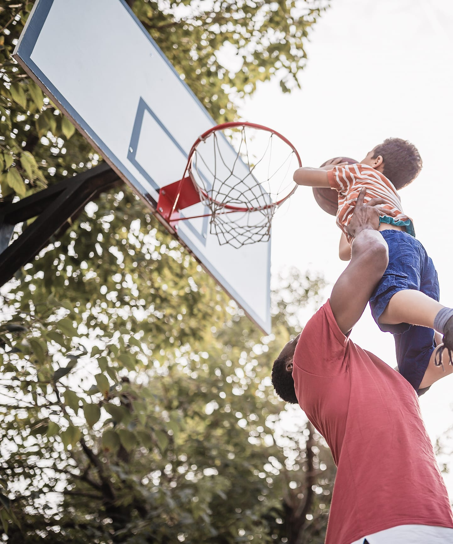 A father raises his young child up to the rim to slam dunk.