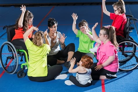 A group of special needs girls play happily in a circle in a gymnasium.
