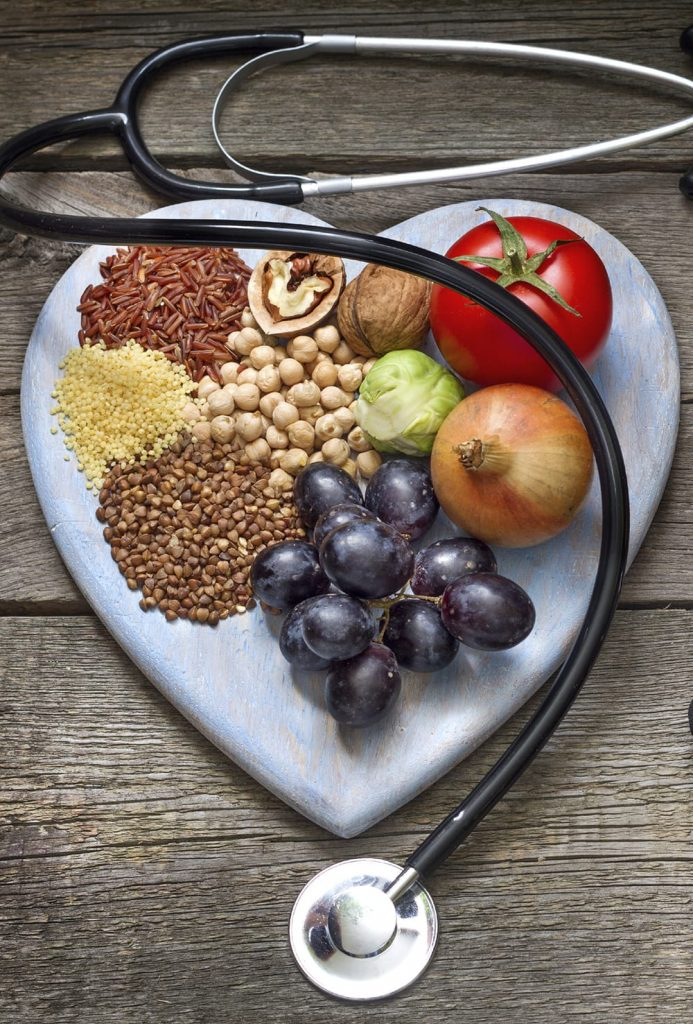 A heart shaped plate holds fruits and grains, and a stethoscope sites around it.