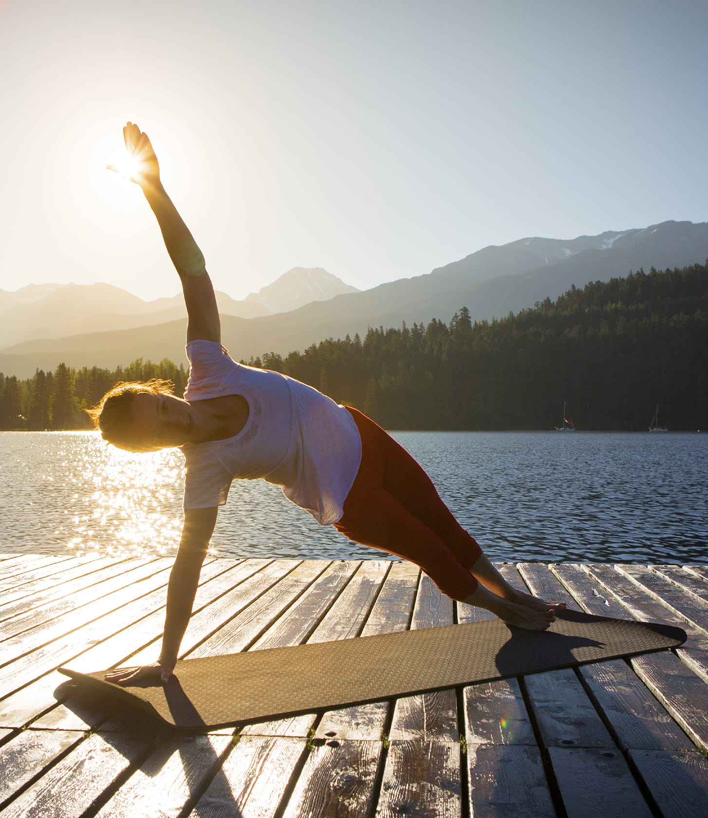 A woman practices yoga on a pier while the sun rises.