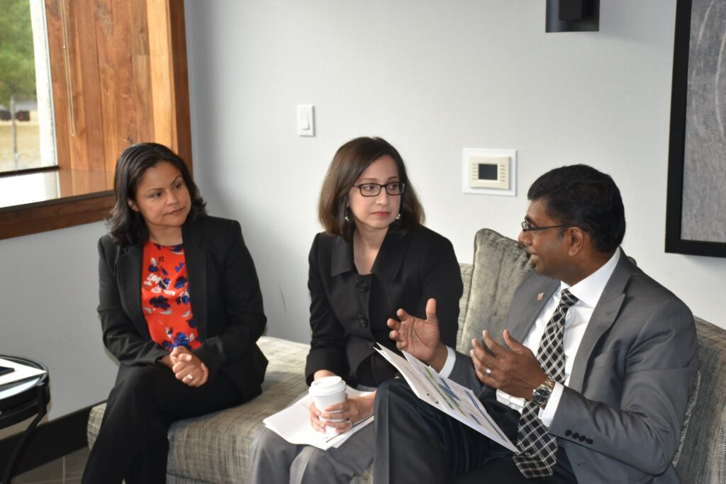 Former Board President Monica Morales looks on as Board President Dr. Susan Kansagra speaks with Dr. Bala Murugan about policy initiatives for NACDD in a conference room. They are holding papers and gesturing with their hands.